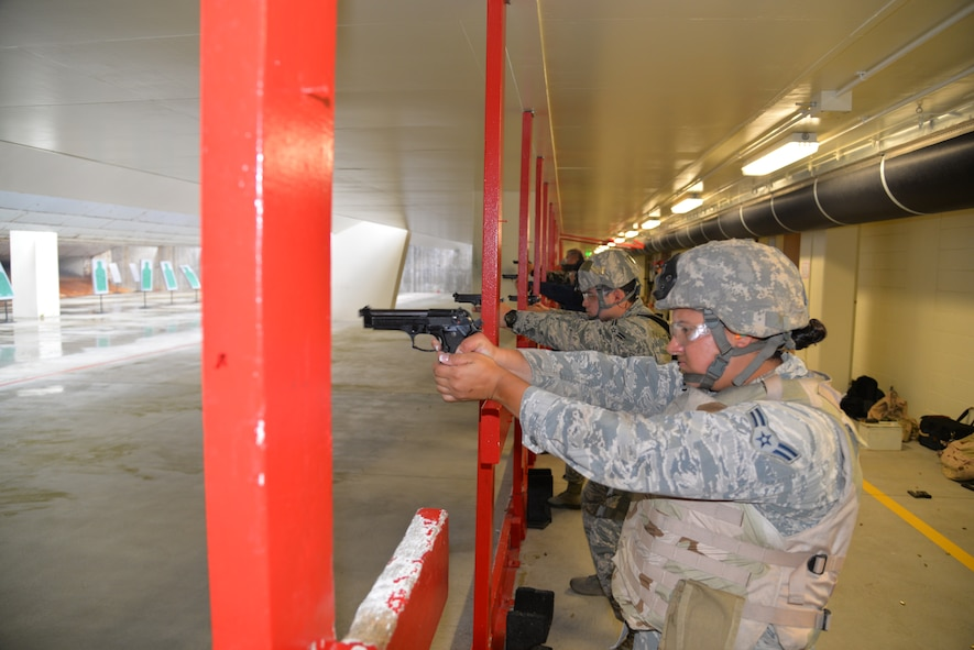Airmen assigned to the 18th Security Forces Squadron fire their M9 pistols during a quick-firing course inside the combat arms training and maintenance facility April 28, 2016, at Kadena Air Base, Japan. Defenders fire their assigned pistols regularly along with other mission-specific training and use the CATM range to ensure success. (U.S. Air Force photo by Staff Sgt. Benjamin Sutton)