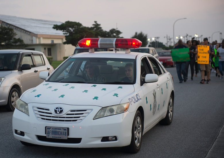 An 18th Wing Security Forces patrol car decorated in teal ribbons leads the Take Back the Night march April 29, 2016, at Kadena Air Base, Japan. The participants marched from the Schilling Community Center parking lot toward Chapel 2 with noise makers and cowbells while chanting, symbolizing survivors reclaiming the night, the time when sexual assaults are most likely to occur. (U.S Air Force photo by Senior Airman Omari Bernard)