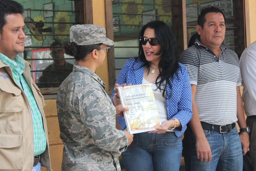 Dr. Doris Cardona (right), Regional Health Director of Copán, presents U.S. Air Force Capt. Amber El-Amin (left), Joint Task Force-Bravo Operations Medical Planner, with an appreciation award for the support given to the people of Copán by JTF-Bravo service members, in Ostumán, Copán, Honduras, April 28, 2016. The Regional Director visited the Medical Readiness Training Exercise location as part of a Civic Leader Engagement between regional key leaders, U.S. Embassy personnel and JTF-Bravo representatives. (U.S. Army photo by Maria Pinel)