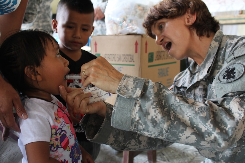 U.S. Army Capt. Katherine Matteson, Joint Task Force-Bravo Medical Element public health nurse, provides de-worming medication to a young girl during a Medical Readiness Training Exercise at Jocotán, Chiquimula, Guatemala, April 29, 2016. Vitamins and de-worming medication were provided for both children and adults during a preventive medicine health class prior to patients seeing the medical and dental providers.  (U.S. Army photo by Maria Pinel)