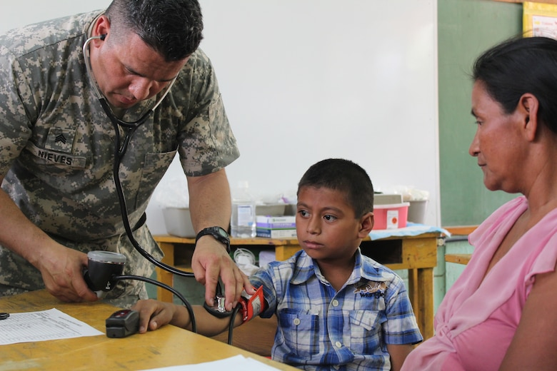 U.S. Army Sgt. Hiram Nieves, Joint Task Force-Bravo Medical Element, examines a young boy during a Medical Readiness Training Exercise at Ostumán, Copán, Honduras, April 28, 2016. The examination is part of a screening process that will determine the type of treatment needed by the patients before visiting the medical providers and pharmacy, where the appropriate treatment and medication is provided free of cost.  (U.S. Army photo by Maria Pinel)