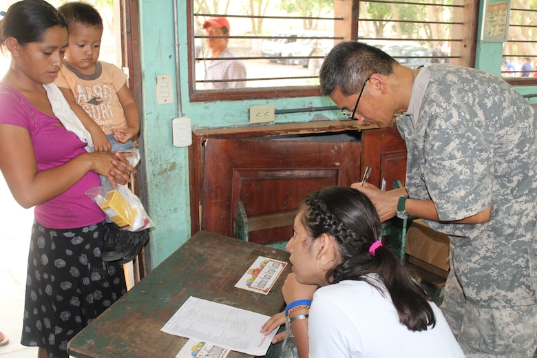 U.S. Army Colonel Sukchan Kim, Joint Task Force-Bravo Medical Element, hands out prescribed medication to a mother and her child during a Medical Readiness Training Exercise in Ostuman, Copán, Honduras, April 28, 2016.  Volunteer translators assisted the U.S. service members during the MEDRETE and facilitated communication between the providers and the patients. (U.S. Army photo by Maria Pinel)