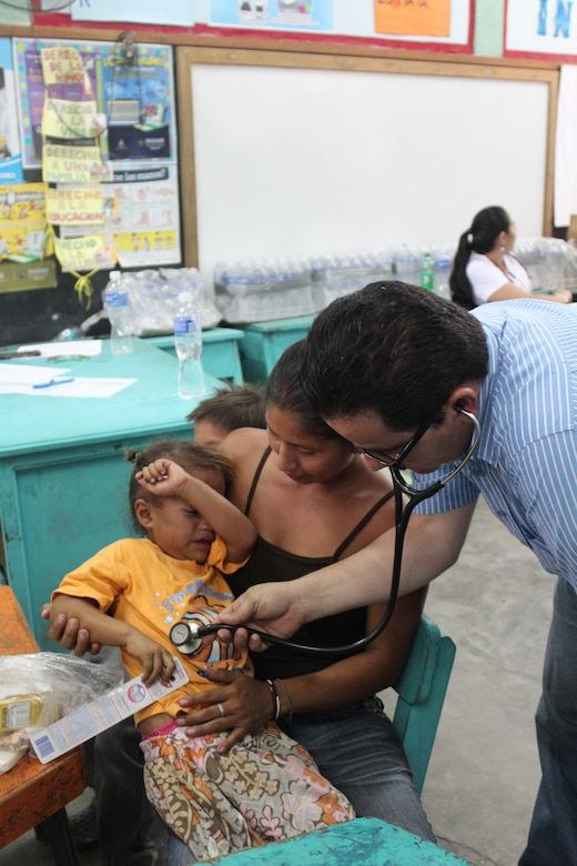 Dr. Carlos Durón, Joint Task Force-Bravo Honduran medical liaison, examines a child during a Medical Readiness Training Exercise in Ostumán, Copán, Honduras, April 28, 2016. As a result of this joint effort between the U.S., Honduras and Guatemala, more than 900 patients were treated during the two-day medical exercise, providing them with basic health care, preventive medicine and orientation, dental services and medication free of cost.  (U.S. Army photo by Maria Pinel)