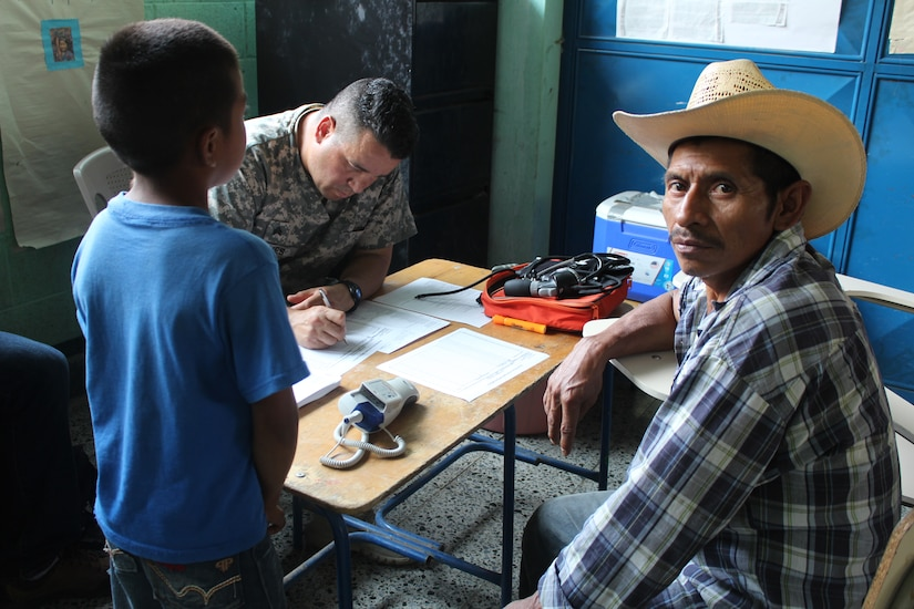 U.S. Army Sgt. Hiram Nieves, Joint Task Force-Bravo Medical Element, fills out a prescription for a Guatemalan man and his son during a Medical Readiness Training Exercise in Jocotán, Chiquimula, Guatemala, April 29, 2016. The designated area for the MEDRETE has high rates of malnutrition and parasitic infections that can lead to anemia. (U.S. Army photo by Maria Pinel)