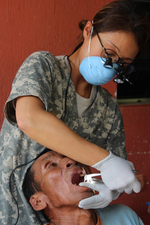 U.S. Army Major Margaret Novicio, Joint Task Force-Bravo Medical Element, performs a tooth extraction on a Guatemalan man during a Medical Readiness Training Exercise in Ostumán, Copán, Honduras, April 28,2016. Dental care is one of many services provided during a MEDRETE, which also includes an initial health class, basic medical attention and access to a pharmacy.  (U.S. Army photo by Maria Pinel)