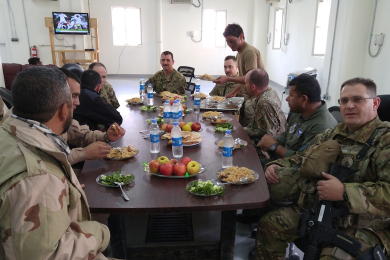 U.S. advisors from Train Advise Assist Command - Air and Afghan students enjoy a lunch together in an Afghan dining facility to build camaraderie and rapport November 22, 2015. Afghan air force students receive on-the-job training supervised by U.S. Air National Guard and Coalition advisors during real-world cargo and passenger sorties. (Some faces are blurred for security reasons) (U.S. Air National Guard photo by Master Sgt. Christopher Coarse, 538th Air Expeditionary Wing/released)