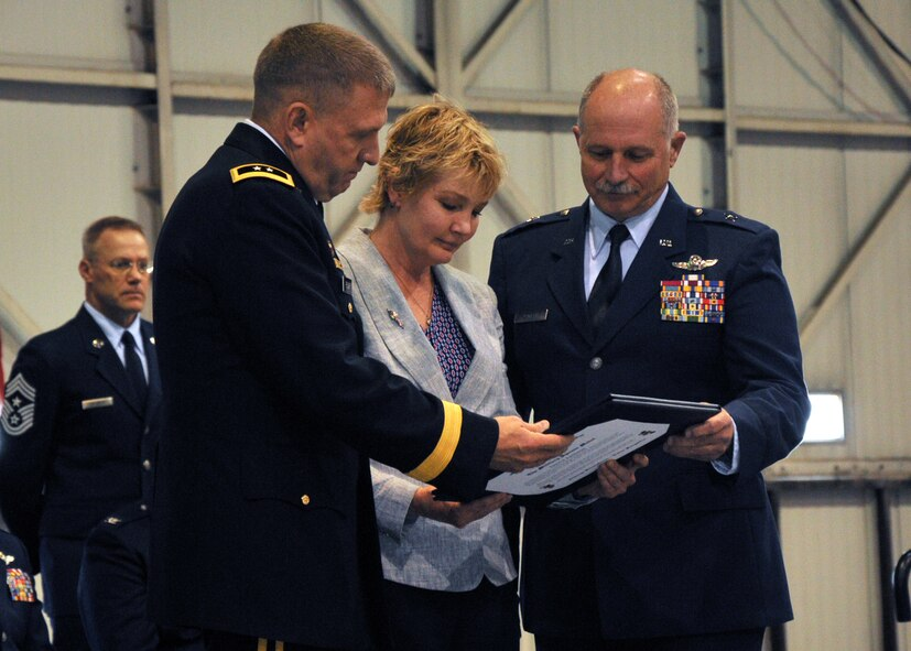 Maj. Gen. Timothy A. Reisch presents Dawn Jamison, wife of Brig. Gen. Matthew P. Jamison, Assistant Adjutant General for Air, HQ SDANG, a certificate of appreciation at a retirement ceremony held on May 1, 2016.  Jamison retires after 37 years with the South Dakota Air National Guard.(U.S. Air National Guard photo by Staff Sgt. Duane Duimstra/released