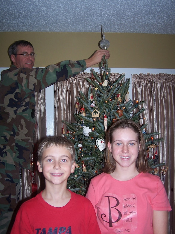 "Retired Col. Robert Moriarty and his children, Ryan and Lauren, decorate for Christmas in the living room of their home at MacDill Air Force Base, Florida in December 2006. Like many military families, Moriarty missed a number of holidays with his family during his active-duty years. ""The home is the heart of a family — it's where celebrations take place and memories are made. Our Airmen and their families deserve to live and make memories in quality homes,"" said Moriarty, who today serves as the Air Force Civil Engineer Center's Installations Director and housing privatization program execution office. (Photo courtesy of the Moriarty family)"