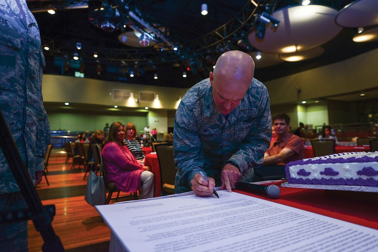 Col. Andrew Hansen, 51st Fighter Wing commander, signs Spouse Appreciation Day proclamation, May 6, 2016, at Osan Air Base, Republic of Korea. The Airman and Family Readiness Center hosted a free lunch and provided spouses with tokens of appreciation from agencies around base in recognition of their contributions to mission success.  (U.S. Air Force photo by Senior Airman Victor J. Caputo/Released)