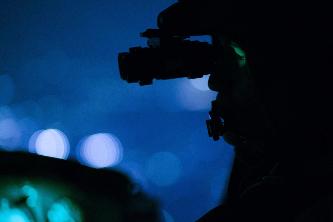 Capt. Jonathan Bonilla, a 459th Airlift Squadron UH-1N Huey pilot, performs a visual confirmation using night vision goggles during a night training sortie over Tokyo, April 25, 2016. The 459th AS frequently trains on a multitude of scenarios in preparation for potential real-world contingencies and operations. (U.S. Air Force photo/Yasuo Osakabe)