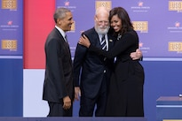 First Lady Michelle Obama hugs former Late Show Host David Letterman as President Barack Obama looks on during the comedy show celebrating the 75th anniversary of the USO and the 5th anniversary of the Joining Forces initiative at Joint Base Andrews near Washington, D.C., May 5, 2016. DoD photo by E.J. Hersom