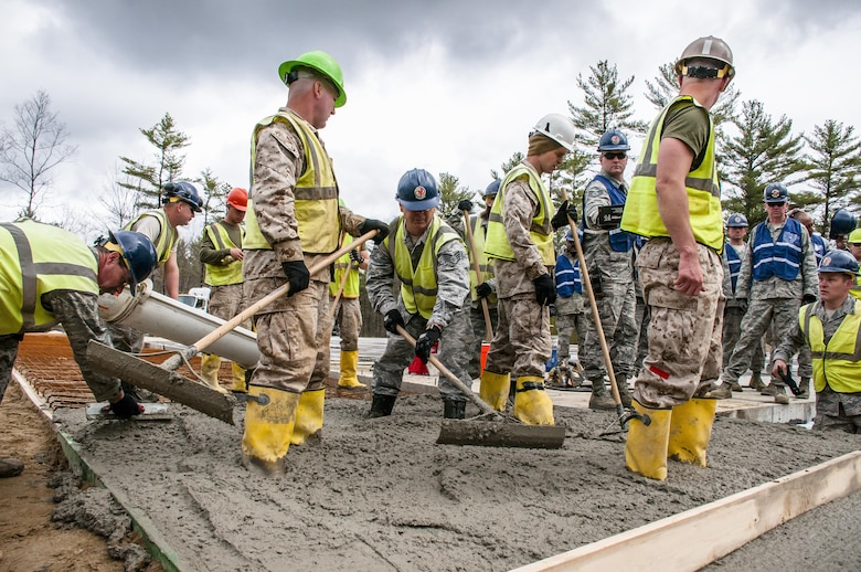 Airmen from the 110th Attack Wing and Marine reservists work together to build a porch for a new dining facility at Camp Hinds, Maine, May 3, 2016. The Airmen participated in the Innovative Readiness Training at Camp Hinds. IRT combines training with community needs, helping Airmen achieve wartime readiness while also helping the community. (U.S. Air National Guard photo/Airman Tiffany Clark)