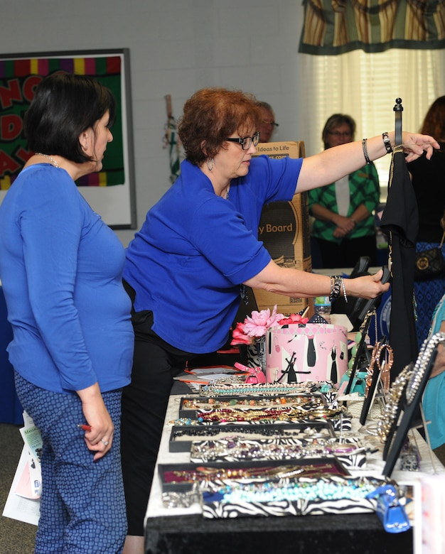Gina Davis, 81st Comptroller Squadron budget analyst, receives a styling tip from Darlene Necaise, a local jewelry stylist, during Pamper Me Day at the Sablich Center May 5, 2016, Keesler Air Force Base, Miss. Keesler's Airman and Family Readiness Center has hosted the event for the past 12 years, offering spouses free manicures, hair styling tips and information and business booths. (U.S. Air Force photo by Kemberly Groue)