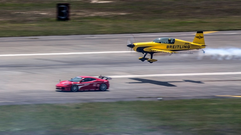 Yoshihide Muroya takes off as he races a Ferrari down the taxi way during the Marine Corps Air Station Iwakuni Friendship Day 2016 Air Show, May 5, 2016. As the first Asian pilot in the Red Bull Air Race World Championship in 2009, Yoshihide has helped raise the popularity of the sport in East Asia, particularly in his home country of Japan. This annual event showcases a variety of static displays, aviation performances and demonstrations, and provides food and entertainment for guests of the largest single-day event in Iwakuni.