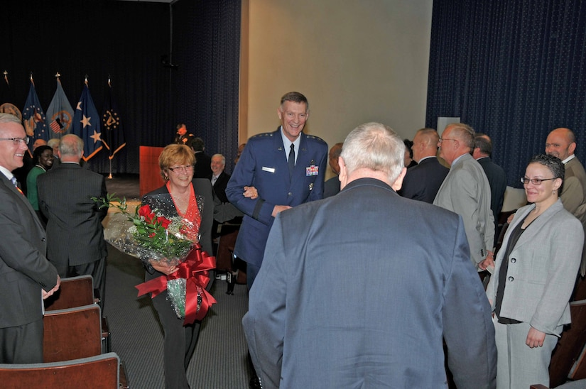 Ginger Pribble, who has been married to DLA General Counsel Fred Pribble for more than 30 years, is escorted from Pribble's retirement ceremony by DLA Director Air Force Lt. Gen. Andy Busch. Photo by Teodora Mocanu