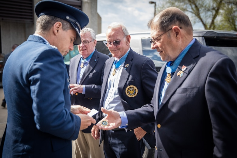 """Medal of Honor Recipient, Mr. Harold """"Hal"""" Fritz (right), exchanges coins with Col. Anthony Polashek (left), 934th Airlift Wing commander, upon his and fellow Medal of Honor Recipients' (center right), Mr. Robert Patterson and Mr. Thomas Kelley, arrivial at the Minneapolis-St. Paul Air Reserve Station, Minn.  The Medal of Honor Meet and Greet  honors military, law enforcement, and first responders affiliated with assisting the Twin Cities 2016 hosting of the Congressional Medal of Honor Convention, set for October of this year.  (U.S. Air Force photo by Shannon McKay)"""