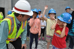 An Archer Western official answers a question from a Diamond Elementary School first-grader at the construction site of the new school May 3. Thirteen contest winners of Archer Western Contractor's poster contest toured the site currently under construction at Fort Stewart, Georgia. Diamond students from kindergarten through sixth-grade submitted posters emphasizing safety themes in recognition of Safety Week celebrated May 2-6. The winning submissions were printed on the firm's calendar that will be available throughout the Fort Stewart community.