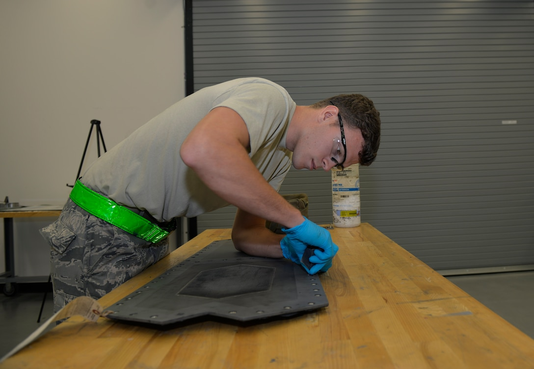 Senior Airman Tyler Quayle, 33rd Maintenance Squadron low observable maintenance journeyman, cleans the slot of an F-35A Lightning II panel before replacing a grommet at Eglin Air Force Base, Fla., Fla., April 28, 2016. The panel must be prepared with a cleaning agent to ensure adhesives can properly bond to the surface keeping parts in place. (U.S. Air Force photo/Senior Airman Andrea Posey)