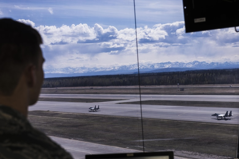 U.S. Air Force Senior Airman Eric Smith, a 354th Operations Support Squadron air traffic controller, watches two F-15 Eagle tactical fither jets assigned to the 67th Fighter Squadron, Kadena Air Base, Japan, May 5, 2016, during RED FLAG-Alaska (RF-A) 16-1. RF-A usually brings various airframes into the mission which, adds complexity to the air traffic controllers' mission. (U.S. Air Force photo by Staff Sgt. Joshua Turner/Released)