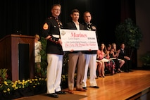 Staff Sgt. Dalton Miller, a canvassing recruiter with Recruiting Station Orlando, and Capt. Kevin Lowe, executive officer for RS Orlando, presents Gavin Rogers, a senior at Steinbrenner High school, the NROTC Marine Option Scholarship during an awards ceremony May 5, 2016. Rogers will be granted the opportunity to serve his country as a Marine officer upon completion of his degree. (Official Marine Corps photo by Sgt. Brian A. Stevens/Released)