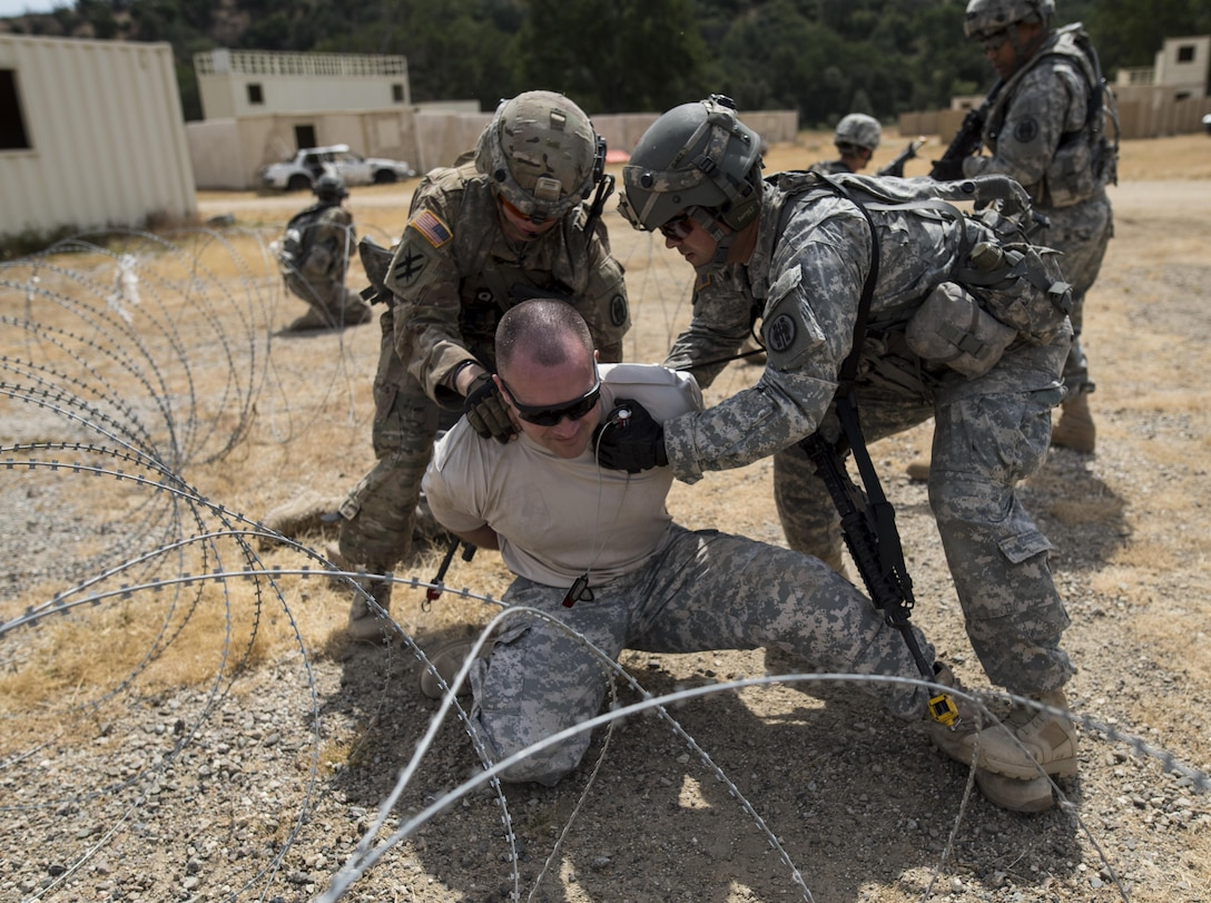 A team of U.S. Army Reserve military police Soldiers from the 56th Military Police Company (Combat Support), of Mesa, Arizona, detain a high-value target, played by Capt. Scott Little, with the 181st Infantry Brigade, of Winnipeg, Canada, during a cordon and search training lane at Fort Hunter-Liggett, California, May 4. Approximately 80 units from across the U.S. Army Reserve, Army National Guard and active Army are participating in the 84th Training Command's second Warrior Exercise this year, WAREX 91-16-02, hosted by the 91st Training Division at Fort Hunter-Liggett, California. (U.S. Army photo by Master Sgt. Michel Sauret)