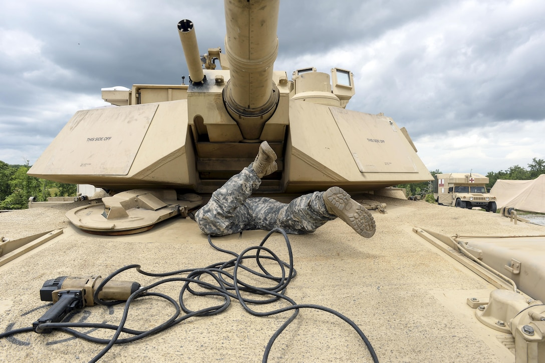 Army Pfc. Harlan Troutman scrambles into the driver's compartment of an M1A1 Abrams tank during the Gen. Gordon Sullivan Cup best tank crew competition at Fort Benning, Ga., May 3, 2016. Troutman is assigned to the Tennessee Army National Guard's H Troop, 2nd Squadron, 278th Armored Cavalry Regiment. Army photo by Sgt. 1st Class Jon Soucy