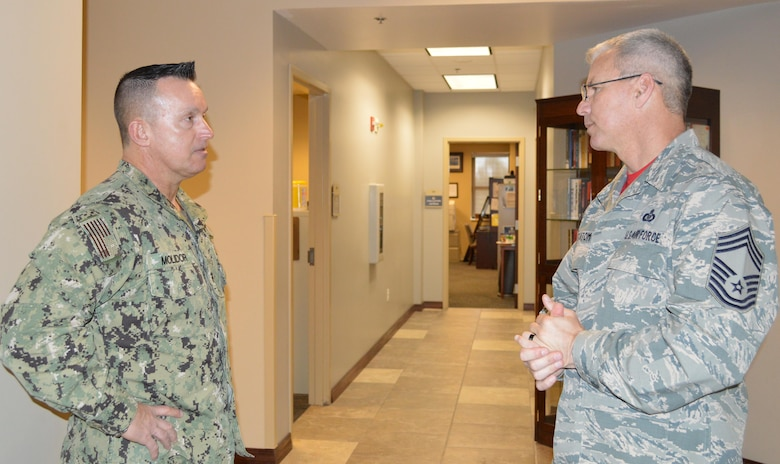 Navy Fleet Master Chief Terrence Molidor, North American Aerospace Defense Command and United State Command Senior Enlisted Leader, talks with U.S. Air Force Chief Master Sgt. Billie Statom Jr., 1st Air Force (Air Forces Northern) Operations Directorate Chief Enlisted Manager, prior to a senior enlisted call May 6 at the Killey Center here. During his visit, Mollidor provided audience members with a current command perspective and answered questions from the audience. (Photo by Mary McHale)