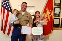 Capt. Gregg Petrisevac, operations officer with the 1st Marine Corps District, poses for a photo with his family after receiving the Navy and Marine Corps Commendation Medal for his accomplishments while serving at the district. (U.S. Marine Corps photo by Cpl. Brandon Thomas/ released)