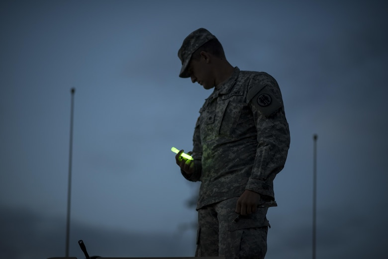 Spc. Bradley Schopf, a U.S. Army Reserve military police Soldier with the 341st MP Company, of Tracy, Califonia, holds a glow stick as he prepares for a mounted crew-served weapon night fire qualification table at Fort Hunter-Liggett, California, May 3. The 341st MP Co. is one of the first units in the Army Reserve conducting a complete 6-table crew-serve weapon qualification, which includes firing the M2, M249 and M240B machine guns both during the day and night. (U.S. Army photo by Master Sgt. Michel Sauret)