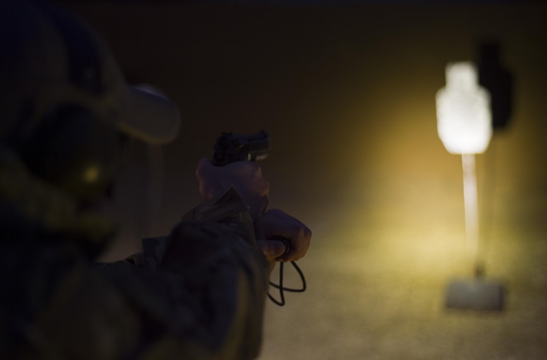 An Air Force Special Operations Command Air Commando practices engaging targets with his M9 pistol and flashlight during a nighttime weapons drill at a firing range near Baker, Fla., Feb. 24, 2016. The irregular nature of AFSOC's mission sometimes require air crews to operate in austere conditions downrange, which prompted the creation of the Air Commando Field Skills Course. (U.S. Air Force photo by Airman 1st Class Kai White)