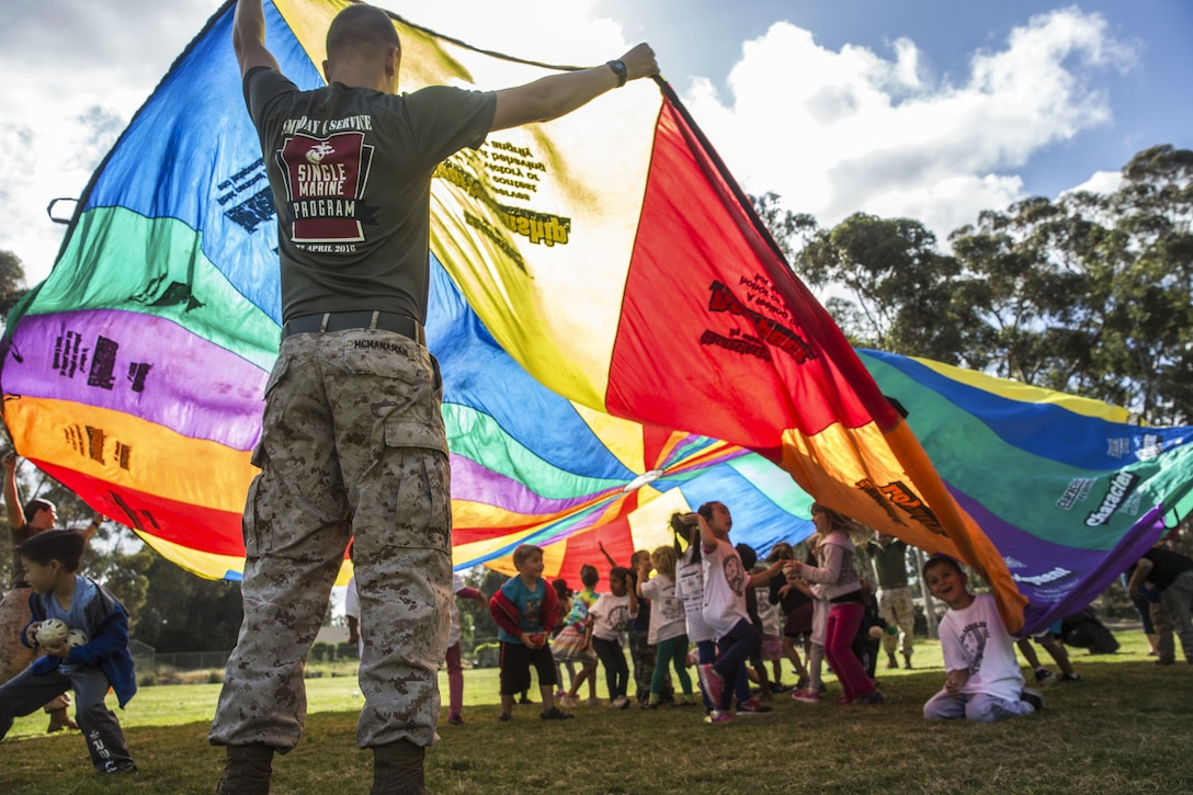 Marine Corps Lance Cpl. Chase McManaman holds a parachute during an activity at an elementary school in San Diego, April 29, 2016. Marines volunteered for a fitness challenge, which allowed children and Marines to complete a series of exercise stations during the school day. McManaman is a volunteer with the Single Marine Program at Marine Corps Air Station Miramar. Marine Corps photo by Sgt. Lillian Stephens