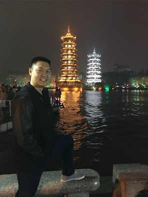 Capt. Raymond Zhang, 22nd Airlift Squadron pilot, poses for a photo in Guilin, China, with illuminated pagodas in the background. Zhang went to China in March to serve as a translator as part of an Air War College visit to the Asian nation. (Courtesy photo)