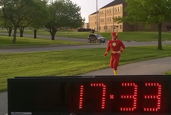 A masked runner crosses the finish line in first place during the 5K Race for Respect at Whiteman Air Force Base, Mo., April 29, 2016. Members of Team Whiteman are encouraged to act like superheroes by choosing to step up, stand up and speak up. (Courtesy photo)