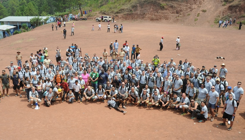 Volunteers from Joint Task Force-Bravo pose for a group photo after distributing 150 bags of food weighing 20 pounds apiece to the 172 families of Montaña La Oki, a small village located in the mountains east of Comayagua, Honduras, during Chapel Hike 67, April 30, 2016. During the visit to Montaña La Oki, U.S. service members had the opportunity to watch local school children perform cultural dances, play soccer and hand out the bags of food to villagers as well as some Hondurans who traveled to the location on horseback from the surrounding mountains. (U.S. Air Force photo by Capt. David Liapis/Released)