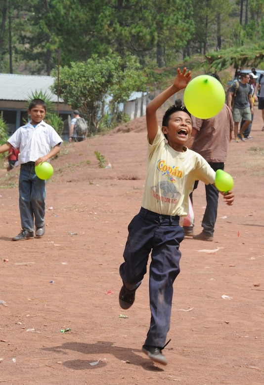A Honduran boy from the village of Montaña La Oki, located in the mountains east of Comayagua, Honduras, plays with a balloon given to him by one of the 158 military and civilian members of Joint Task Force-Bravo and volunteer firefighters from the local area who hiked 7.4 miles roundtrip to deliver 3,000 pounds of food to 172 families in the village April 30, 2016. During the visit to Montaña La Oki, U.S. service members had the opportunity to watch local school children perform cultural dances, play soccer and hand out the bags of food to villagers as well as some Hondurans who traveled to the location on horseback from the surrounding mountains. (U.S. Air Force photo by Capt. David Liapis/Released)