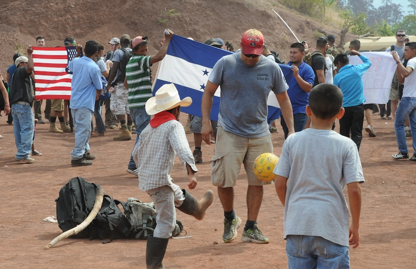 U.S. Air Force Capt. Jesus Lopez, Joint Task Force-Bravo personnel officer, plays soccer with children from Montaña La Oki, a small village located in the mountains east of Comayagua, Honduras, while local village men hold U.S. and Honduran flags welcoming the participants of Chapel Hike 67 and the 3,000 pounds of food they carried 3.4 miles up the mountain, April 30, 2016. During the visit to Montaña La Oki, U.S. service members had the opportunity to watch local school children perform cultural dances, play soccer and hand out the bags of food to villagers as well as some Hondurans who traveled to the location on horseback from the surrounding mountains. (U.S. Air Force photo by Capt. David Liapis/Released)