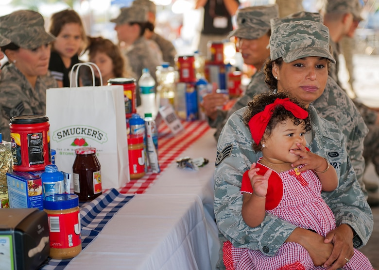 Staff Sgt. Erica Veras, 53rd Wing, holds her daughter close during the 96th Force Support Squadron's Mission Breakfast May 4 at Eglin Air Force Base, Fla. The Eglin commissary won a photo contest that awarded free breakfast to all Eglin members.  (U.S. Air Force photo/Ilka Cole)