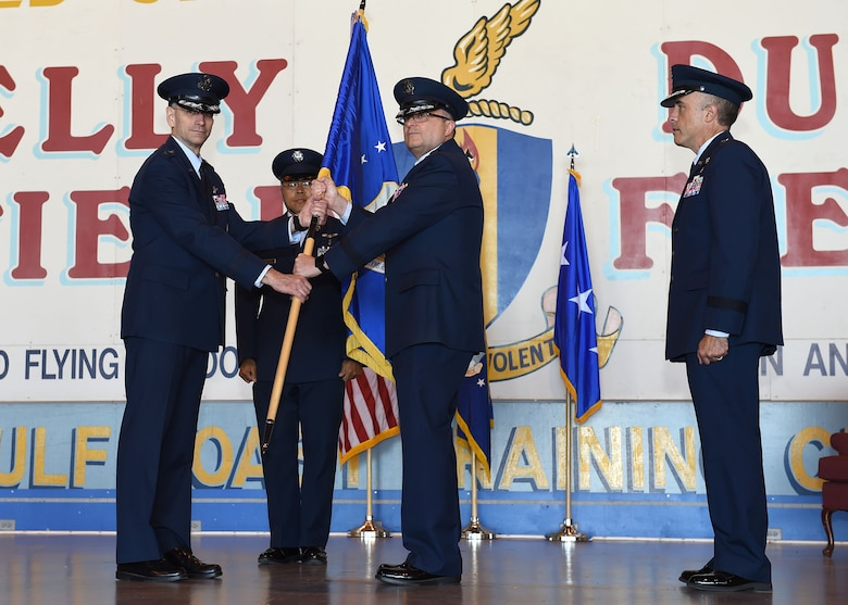 Lt. Gen. Mark A. Ediger (left), Surgeon General of the Air Force, receives the Air Force Medical Operations Agency guidon from Brig. Gen. Lee E. Payne (center), former AFMOA commander, during a May 6 change of command ceremony at Port San Antonio. In military tradition, the passing of a unit's guidon signifies relinquishing or accepting command of that unit.