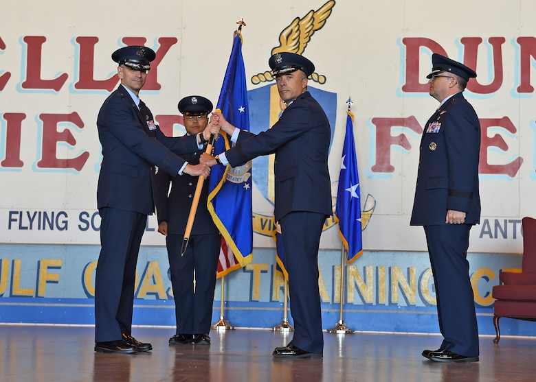 Lt. Gen. Mark A. Ediger (left), Surgeon General of the Air Force, passes the Air Force Medical Operations Agency guidon to Brig. Gen. Robert I. Miller (center), incoming AFMOA commander, during a change of command ceremony at Port San Antonio, May 6. In military tradition, the passing of a unit's guidon signifies relinquishing or accepting command of that unit. (U.S. Air Force photo / Tech. Sgt. Christopher Carwile.)
