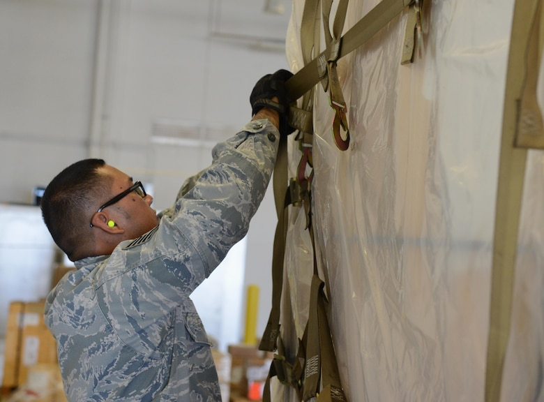 Tech. Sgt. Rolando Jose, 44th Aerial Port Squadron air transportation special handler, breaks down a cargo pallet May 2, 2016, at Andersen Air Force Base, Guam. Jose serves in the U.S. Air Force Reserve and works in a civilian capacity at Antonio B. Won Pat International Airport as a Transportation Security Administration agent. (U.S. Air Force photo by Airman 1st Class Arielle Vasquez/Released)