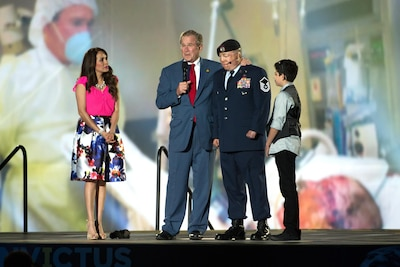 Former President George W. Bush stands on-stage with Air Force Master Sgt. Israel Del Toro and his family during the opening ceremony to the 2016 Invictus Games in Orlando, Fla., May 8, 2016. In the background, there's a photo of Bush visiting Del Toro in the hospital. DoD photo by EJ Hersom