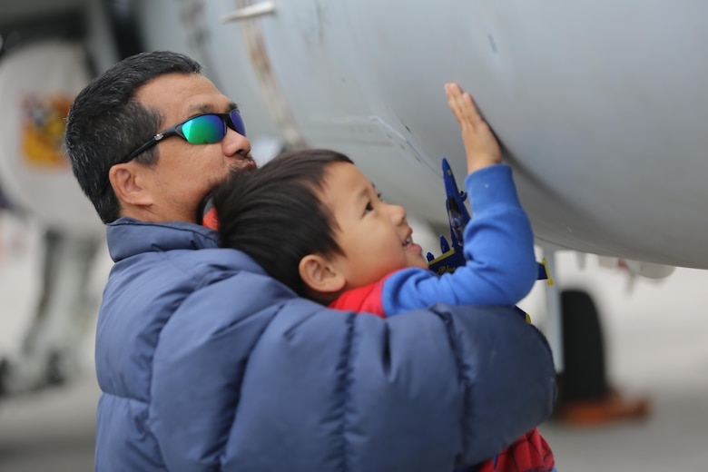 "A father hoists his son to touch the side of an aircraft at the 2016 Marine Corps Air Station Cherry Point Air Show – ""Celebrating 75 Years"" at MCAS Cherry Point, N.C., April 30, 2016. This year's air show celebrated MCAS Cherry Point and 2nd Marine Aircraft Wing's 75th anniversaries and featured 40 static displays, 17 aerial performers and a concert. (U.S. Marine Corps photo by Lance Cpl. Mackenzie Gibson/ Released)"
