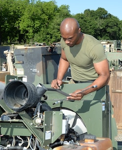Sgt. Frederick Graham, heavy equipment engineer maintenance chief, Organic Maintenance Unit, Marine Corps Logistics Command, removes reusable parts from scrapped equipment for shipment to installations around the Marine Corps. Graham said some of the parts may be requested for use by other branches of service as well. The sergeant, who was recently selected as LOGCOM's Noncommissioned Officer of the Quarter, said one of the highlights of his military career was meeting one of the original Montford Point Marines, Henry L. Jackson, a World War II veteran and retired U.S. Air Force master sergeant. Jackson, a Congressional Gold Medal recipient, was one of the 20,000 African-American Marines to attend basic training at Montford Point, North Carolina, between 1942 and 1949.