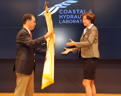 Jose Sanchez, director of the Coastal and Hydraulics Laboratory, U.S. Army Engineer Research and Development Center, presents the Scientific and Professional flag to Dr. Jane McKee Smith.  Smith began her distinguished career with ERDC in 1983.