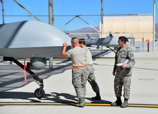 Tech. Sgt. Remington, 432nd Maintenance Group quality assurance inspector, watches as a 432nd Aircraft Maintenance Squadron Tiger Aircraft Maintenance Unit team checks the weight and balance of an MQ-1 Predator May 3, 2016. QA plays an essential role in completing the maintenance mission by ensuring maintainers follow technical orders and complete maintenance right. Missing minor mistakes or making maintenance errors can result in serious damage to aircraft and personnel. (U.S. Air Force photo by Senior Airman Christian Clausen/Released)