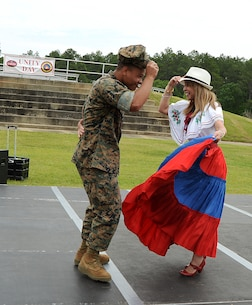 Cpl. Peter Hernandez-fuentes, adjutant clerk, Marine Corps Logistics Command, dances with Lydia Olds, Spanish teacher, International Studies Elementary School, Albany, Ga., during the annual Unity Day celebration held recently on Marine Corps Logistics Base Albany. The event is held to educate individuals on diversity and celebrate differences.