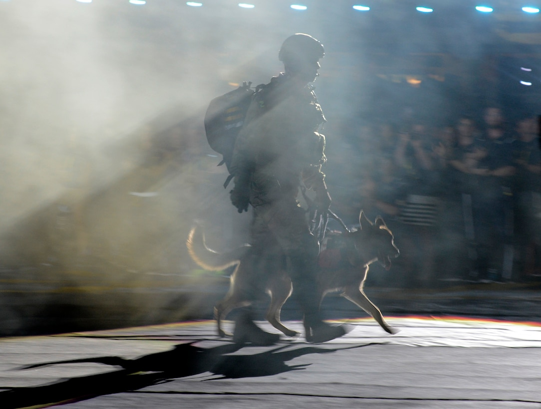 Staff Sgt. August O'Neill walks in the Invictus flag with his service dog, Kai, at the opening ceremony for the Invictus Games 2016 in Orlando, Fla., May 8, 2016. The Invictus Games are composed of 15 nations over 500 military competitors competing in 10 sporting events May 8-12, 2016. (U.S. Air Force photo/Staff Sgt. Carlin Leslie)