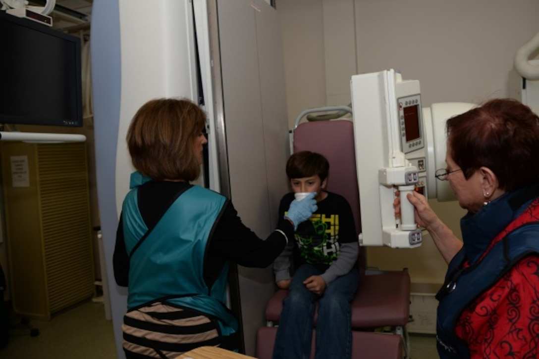 Ms. Suzanne Stinson, 59 MDW Speech-Language Pathologist, performs a swallow study on her patient, Sebastian Kapici.  During a swallow study, various textures of food/liquid are offered to observe real time swallowing to rule out aspiration via a videofluorscopic study. (Courtesy photo)