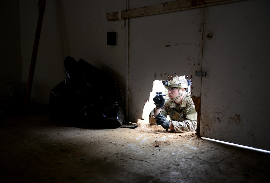 """Airman 1st Class Alex Nona, 60th Civil Engineer Squadron explosive ordnance disposal technician, inspects the interior of an abandoned structure known as the """"bomb factory"""" prior to entry during an exercise May 5th, 2016, at Clear Lake, California. Nona and other EOD technicians were tasked to eliminate numerous improvised explosive devices and a radioactive dispersal device within the abandoned structure. (U.S. Air Force photo by Senior Airman Bobby Cummings)"""