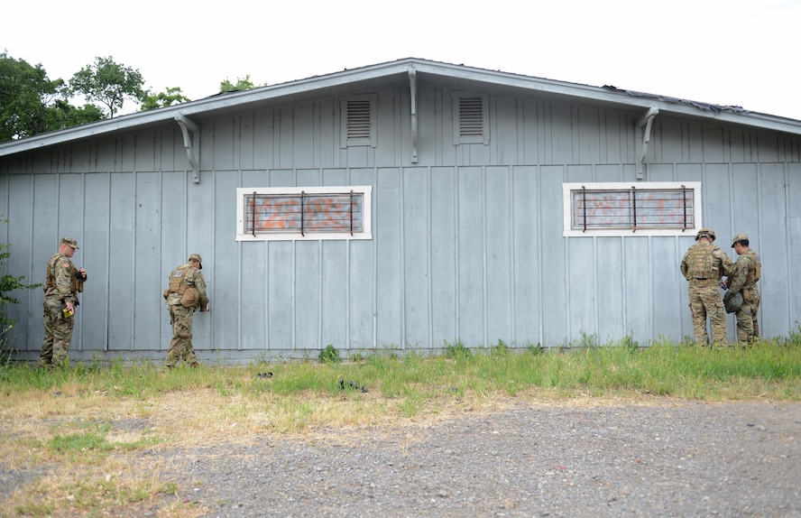 """Soldiers with the 95th Civil Support Team inspect an abandoned building for radiological material May 5th, 2016, at Clear Lake, California. The building was a simulated """"bomb factory"""" during an exercise designed to evaluate a synchronized, multi-agency response to a crisis situation. (U.S. Air Force photo by Senior Airman Bobby Cummings)"""